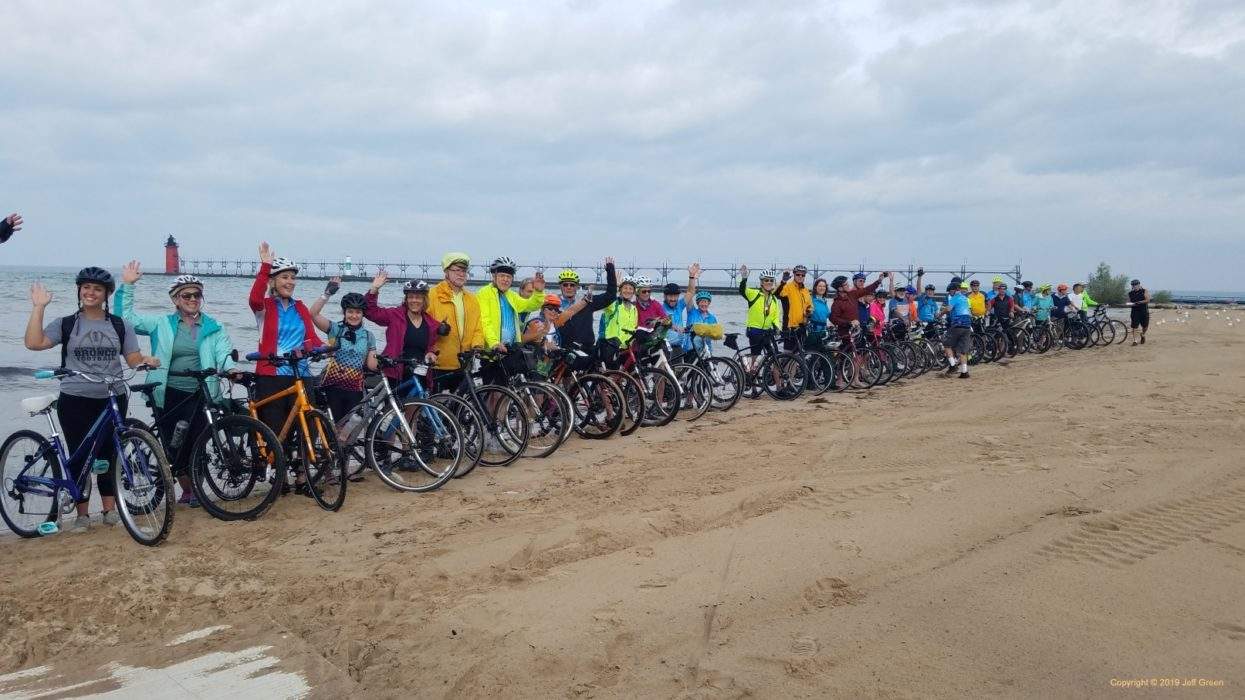 Riders dipping their rear tires in Lake Michigan - their front tires dip into Lake Huron